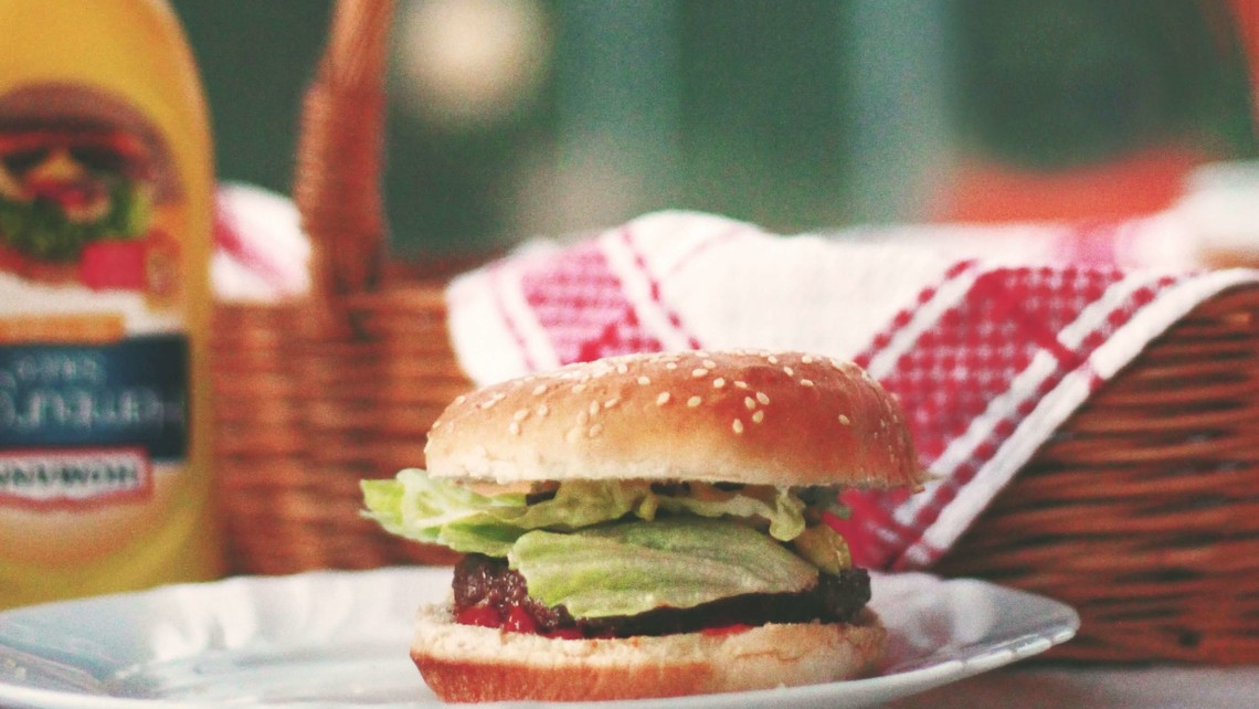 hamburger sits on a plate with mustard and straw basket in the background