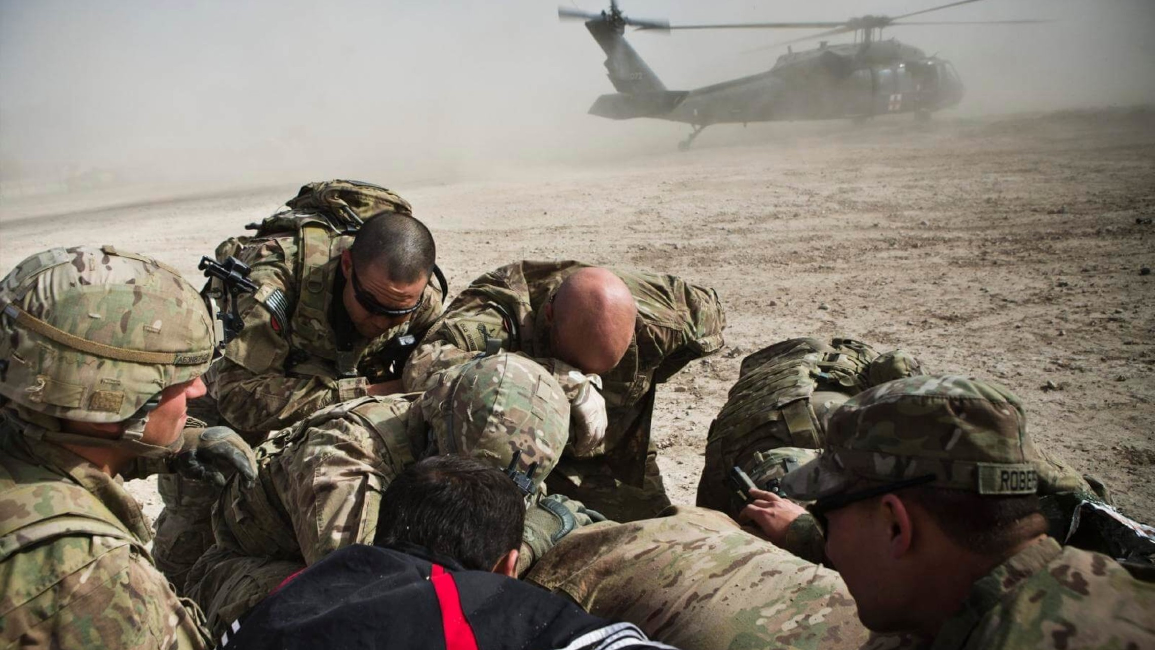 photo of a huddled group of soldiers in the desert in Afghanistan
