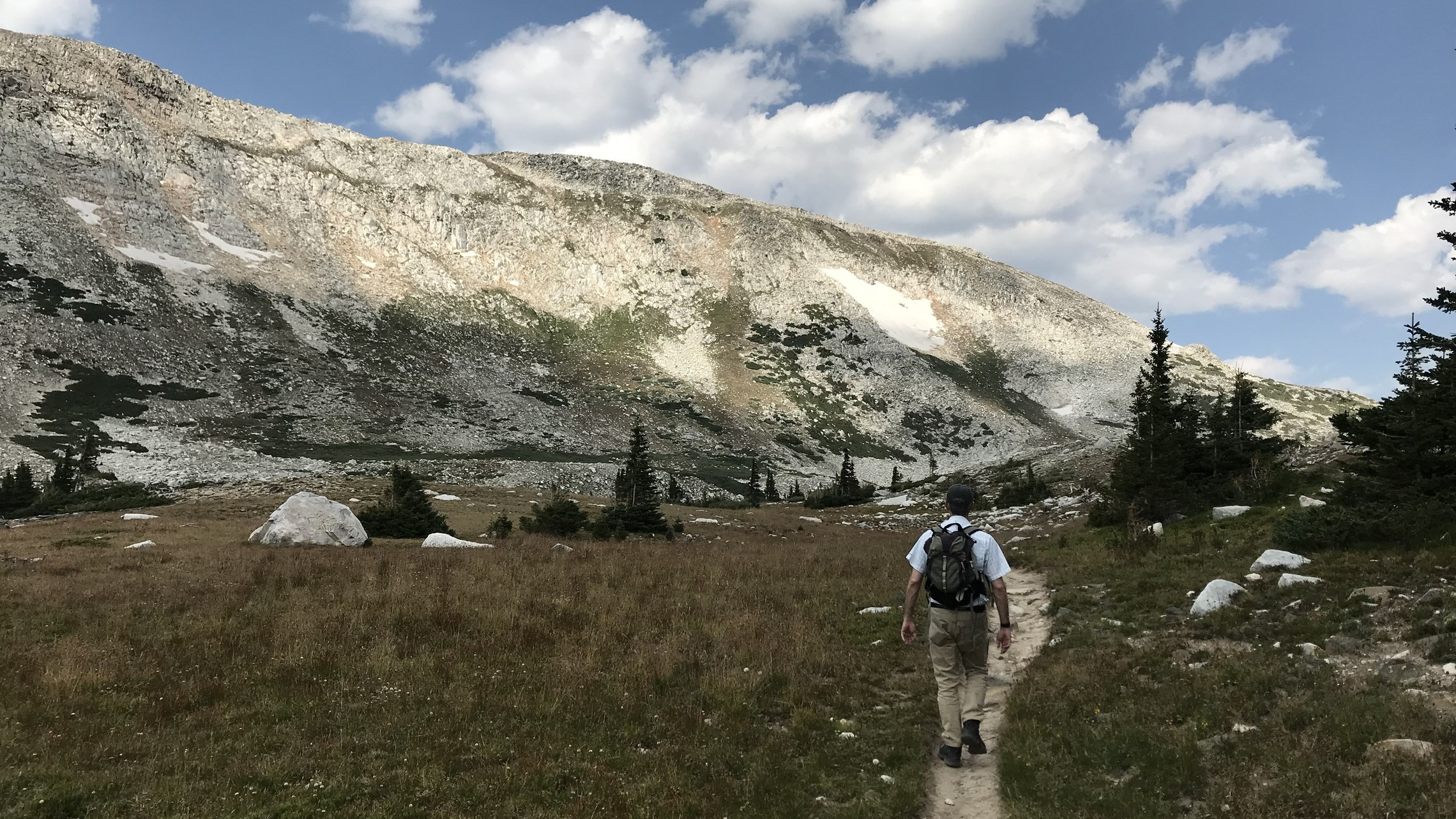 A man on a trail hiking in the mountains